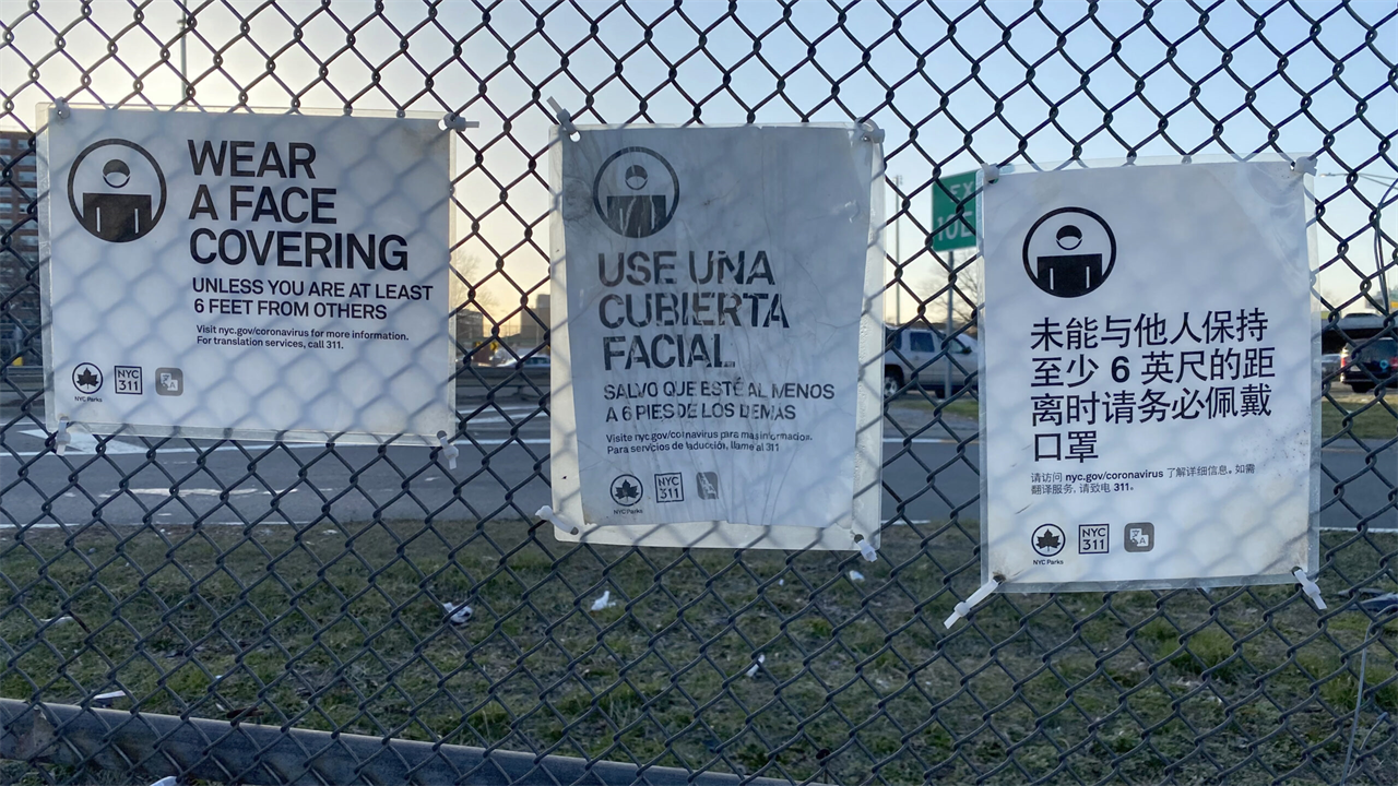 coronavirus precaution signs in multiple languages hang on a fence