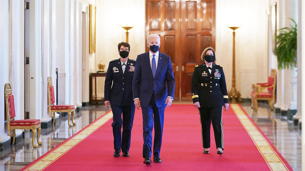 US President Joe Biden (C) arrives, flanked by the nominees to positions as 4-star Combatant Commanders General Jacqueline Van Ovost (L) and Lieutenant General Laura Richardson, to speak during International Women